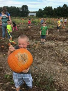 kid holding pumpkin